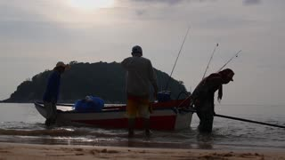 Silhouette of a Fishermen Pulling Fishing Boat on Beach