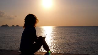 Silhouette of a Woman Relaxing on Beach at Sunset over the Sea.