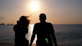 Silhouette of Couple in Love at Sunset on the Beach. Slow Motion.