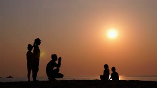 Silhouette of Family Taking Pictures of Kids on Beach at Sunset with Smartphone