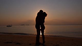 Silhouette of Happy Couple Embracing on Beach at Sunset