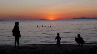 Silhouette of Happy Family on the Beach at the Sunset Time.