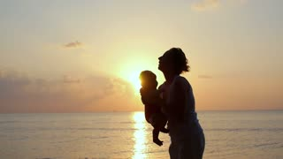 Silhouette of Mother and Baby at Sunset. Slow Motion.