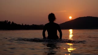 Silhouette of Woman in Sea Enjoying Sunset. Slow Motion.