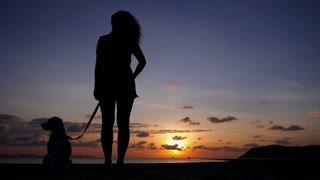 Silhouette of Young Woman with Dog at Sunset at Sea