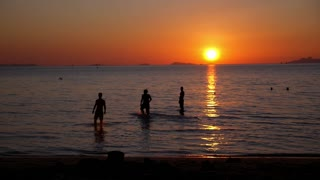 Silhouettes of Happy Young People Swimming in Sea against Sunset.