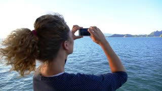 Slow Motion of Woman Taking Photograph with a Smart Phone Camera of Seascape from the Ferry.