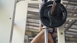 Sports Woman Weight Training on Smiths Machine in Gym