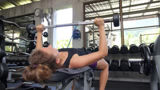 Sporty Woman Lifting Weight in Gym. Exercise and Fitness