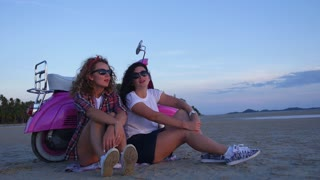 Stylish Hipster Girls with Vintage Scooter on Beach at Sunset