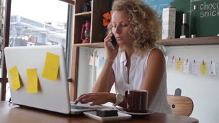 Successful Woman Speaking on Phone Using Laptop in Cafe