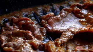 Succulent Roasted Meat Sizzling on Frying Pan. Close up.