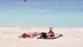 Summer Holidays - Girls in Bikinis Sunbathing on the Beach.