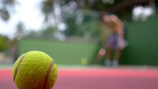 Tennis Ball on Court and Man Playing Tennis. Slow Motion.
