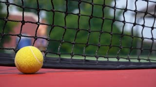 Tennis Ball on the Court Close up with the Net Beyond