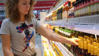 THAILAND, KOH SAMUI, 09.09.2015 - Woman in the Supermarket Shopping for Food, Olive Oil