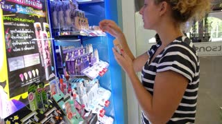 THAILAND, KOH SAMUI, DECEMBER 2014 - Young Woman Chooses Make-up Foundation at Cosmetics Shop