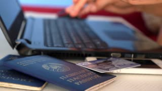 THAILAND, KOH SAMUI, FEBRUARY 2015 - Woman Using Passports, Credit Cards for Buying Tickets Online