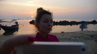 THAILAND, KOH SAMUI, MARCH 2015 - Beautiful Young Woman Taking Selfie on Beach at Sunset. Slow Motion.