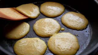 Thick Pancakes being Flipped in Hot Frying Pan.