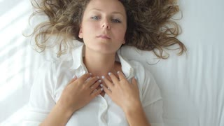 Top View of Young Woman Sending Air Kiss Lying on Bed