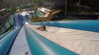 Tourists Having Fun at Water Slide at Waterpark at Sunset.