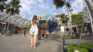 Tourists Sightseeing at Rotating Globe Fountain in Universal Studios. Timelapse.