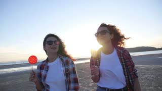 Trendy Girls Walking at Beach at Sunset. Slow Motion.