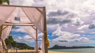 Tropical island beach view and clouds running jn blue sky. 4K time lapse