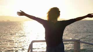 True Happiness. Free Inspired Woman Enjoying Sunrise. Beautiful Woman Embracing the Golden Sunshine Glow of Sunrise with Arms Outspread. Slow Motion.