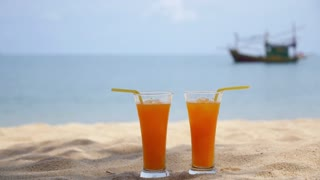 Two Glasses of Orange Juice on Beach and Swimming Couple