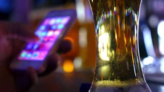 Using Mobile Phone with Beer Glass at Bar Counter