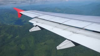 Airplane Landing Over Green Hills Of Laos. View From Plane Illuminator