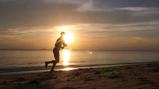 Beach Vacation Lifestyle: Man Silhouette Playing Frisbee at Sunset on Beach