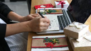 Businesswoman Hands Signing Christmas Card In Office At Workplace