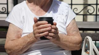 Closeup Of Elderly Woman Holding Coffee To Go