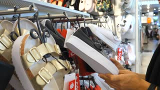 Female Customer Shopping At Shoes Store With Sales