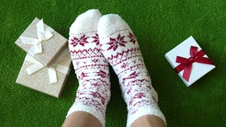 Female Feet In Christmas Socks At Home In Winter Holiday Xmas With Gifts