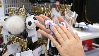 Female Hands Choosing Pink Unicorn Keychain In Shopping Center With Accessories