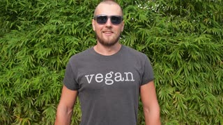 Funny Handsome Man With Vegetables in Vegan T-Shirt Against Violence