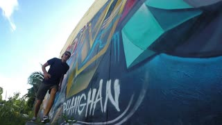 Graffiti Artist Man Jumping Against Painted Urban Wall