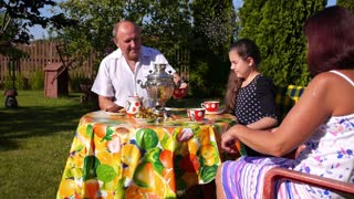 Grandfather and Grandmother with Granddaughter Drinking Tea