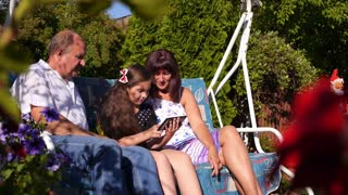 Grandparents and Granddaughter Using Tablet in Summer House