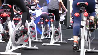 Group of People In Gym Or Fitness Club Exercising On Cycling Machines.