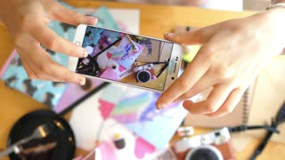 Hands Taking Photos Of Creative Flat Lay of Workspace Desk With Smartphone