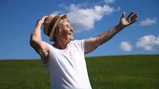 Happy Elderly Woman With Arms Outstretched On Meadow