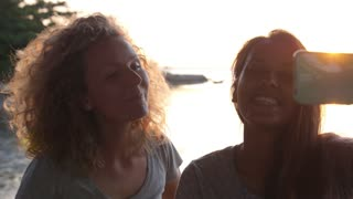 Happy Girls Friends Taking Selfie Together on Beach At Sunset