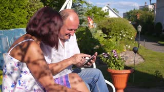Happy Middle-Aged Couple Using Tablet Outdoors
