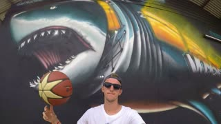 Man with Basketball Ball Against Graffiti Wall