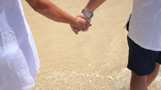 Middle-Aged Couple Holding Hands Walking at Beach